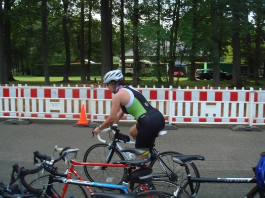 The Wife leaving transition at hometown triathlon in the middle of nowhere.  Note the adorable triathlon onesie and the gorgeous German woman on the gorgeous Italian road bike.